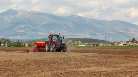 Tractor sowing on empty field, village houses and mountains in background. Reklamní fotografie