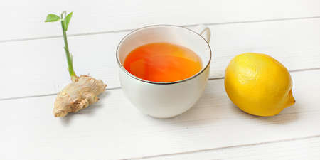 Hot amber tea in porcelain cup, whole lemon and ginger root with green sprout next to it on white boards.