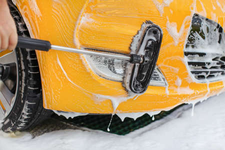 Front bumper and lights of yellow car washed in self serve carwash, brush  moving in white shampoo. Reklamní fotografie