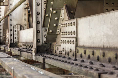 Detail of old rail bridge, large nuts, bolts and rivets visible. Abstract industrial background. Reklamní fotografie