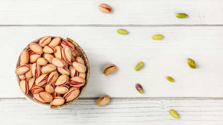 Tabletop view, small bowl with red Turkish pistachios, more nuts scattered on white board desk. Reklamní fotografie