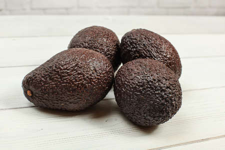 Four brown whole avocados on white boards.