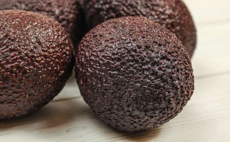 Detail of ripe whole brown avocado, rough skin visible, more avocados on white boards in background.