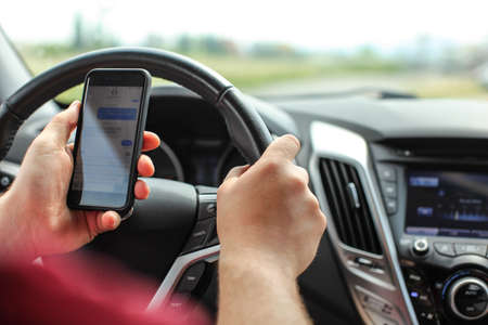 Man checking his text messages while driving. Dangerous texting in car concept. Reklamní fotografie