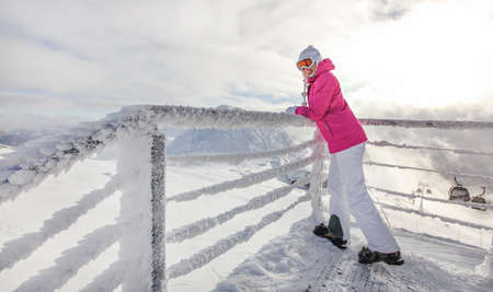 Young woman in pink ski jacket, boots gloves hat and goggles leaning on crystal snow covered fence rail, looking back. Sun shining on top of the mountain piste behind.