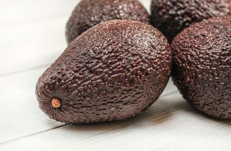 Dark brown ripe avocados on white boards. Close up, detail on skin texture visible. Reklamní fotografie