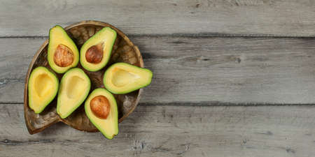 Top down view, Avocados cut in half, seed visible placed on old wooden carved bowl and gray wood desk. Space for text on right. Reklamní fotografie