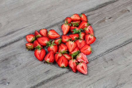 Strawberries cut in half, arranged to shape of heart, placed on gray wood desk.