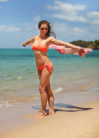Young sporty woman in orange bikini swimwear and sunglasses, walking on beach, holding scarf behind her that is waving in wind.