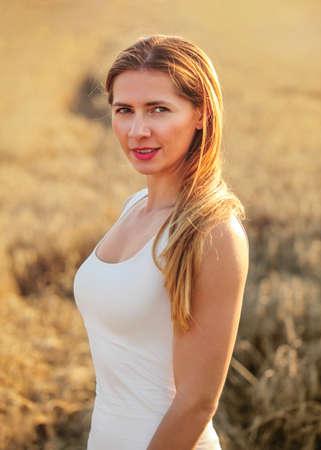 Young brunette woman in white dress, standing in wheat field lit by afternoon sun. Reklamní fotografie