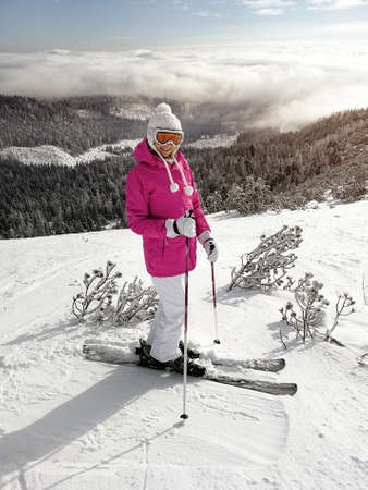 Young woman in pink jacket, skis, ski poles, goggles and hat, posing on the snow covered piste, sun shining to forest behind her.