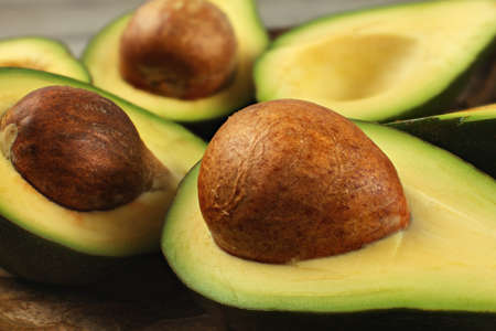 Avocado fruits cut in half, seed visible, close up photo, showing structure on brown pit. Reklamní fotografie