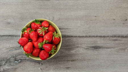 Top down view, small bowl with strawberries on gray wood desk. Space for text on right. Reklamní fotografie