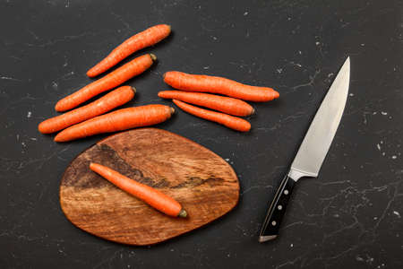 Top down view, orange carrot, chopping board and chef knife next to it, on black marble board.