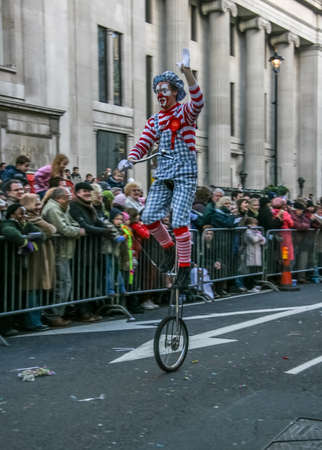 London, United Kingdom - January 1, 2007: Man in clown costume rides unicycle, and waves to cheering crowd, during New Year's Day Parade.