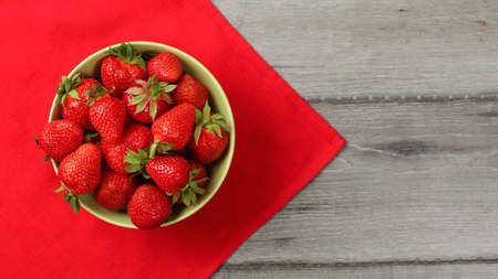 Red ripe strawberries in a small bowl, with tablecloth and gray desk under.