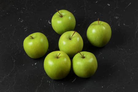 Six green / yellow apples on black marble board.