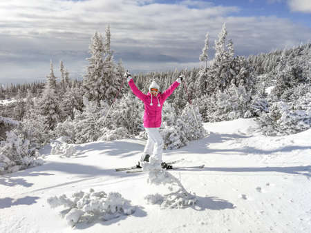 Young woman in pink jacket, boots, ski, poles, goggles and hat, hands in the air, looking happy, snow covered trees behind