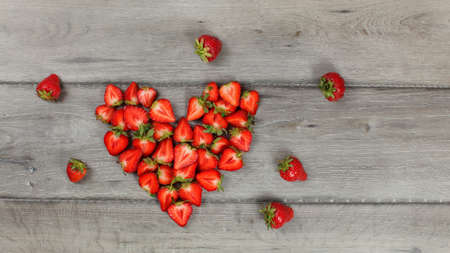 Strawberries cut to halves pieces, arranged in heart shape, on gray wood desk. Top down view. 免版税图像