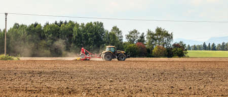 Tractor sowing on empty field, small trees in background. Wide agriculture banner.