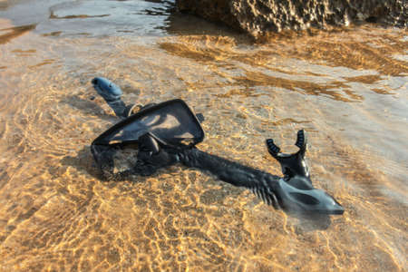 Black snorkelling tube and diving mask / goggles on sand in shallow sea water. 免版税图像