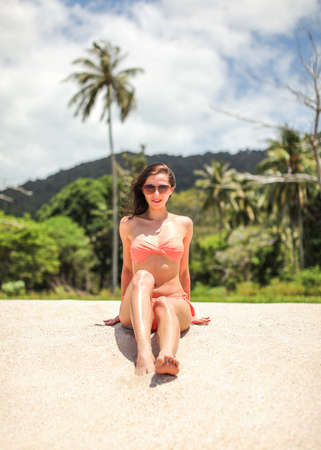 Young woman in bikini and sunglasses sitting on beach sand, looking into camera, palms and sky with clouds behind her. 免版税图像