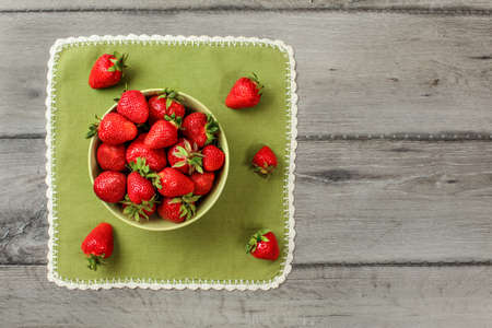 Flat lay view - small bowl with strawberries, some spilled on green tablecloth, gray wood desk under. 免版税图像