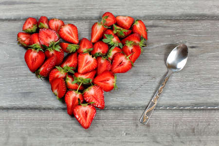 Top down view, heart made from strawberry pieces, silver spoon next to it, on gray wood desk. 免版税图像