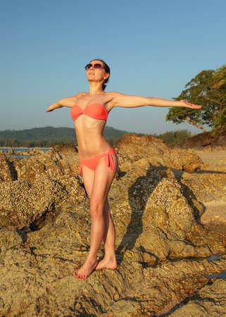 Young slim woman in bikini swim wear and sunglasses, standing on the rocks near beach, arms spread, facing to sun, as if gathering energy. 免版税图像