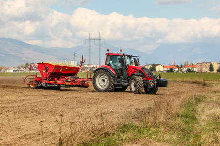 Red tractor sowing, pulling seeder trailer behind, on dry field, some houses and mountains in background.