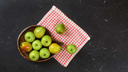 Top down view, green apples and pears in wooden carved bowl, red chequered tablecloth and black marble board under. 免版税图像