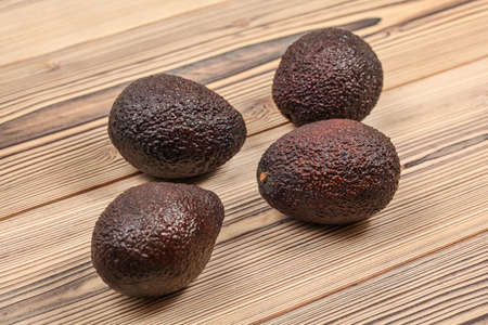 Four dark brown ripe avocados on wooden boards.