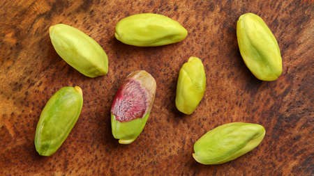 Top down view, green peeled pistachio nuts on wooden board.