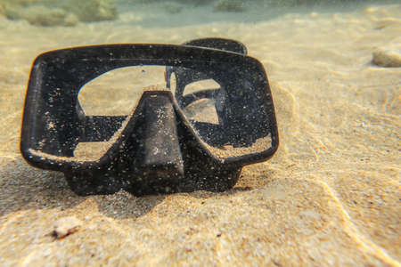 Underwater photo - black diving mask / goggles on sand in shallow water near beach.