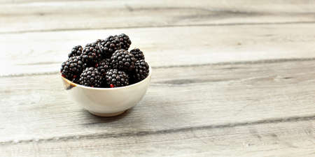 Small bowl with blackberries on wooden desk, space for text on right side. 版權商用圖片