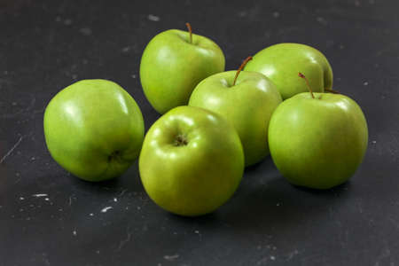 Green / yellow apples on black marble board.