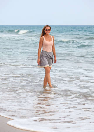 Young woman in skirt, t shirt and sunglasses standing in shallow water on the beach during overcast day, sea behind her.