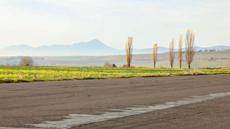 Simple minimal autumn landscape. Asphalt road, meadow, trees with few yellow laves, distant hazy mountain in background.