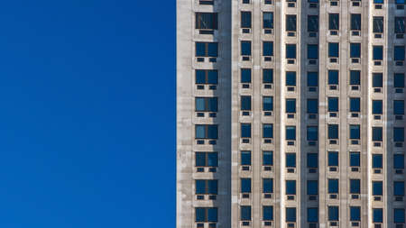 Regular pattern made of rectangular windows on block of flats / offices building. Clear sky (place for text) on left side.