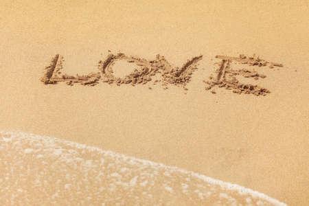 Word LOVE written in wet sand on the beach, sun shining over. 版權商用圖片