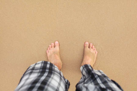 Top down view, man wearing black and white shorts feet in wet sand on beach. Space for text upper part. 版權商用圖片