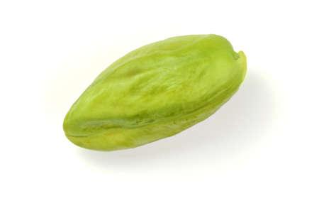 Single green peeled pistachio isolated on white background.