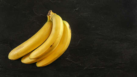 Top down view, bunch of yellow bananas on black board, space for text on right. 版權商用圖片