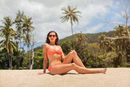Young sporty woman in orange bikini and sunglasses, sitting on the sand near beach, palms, hills and sky behind her.