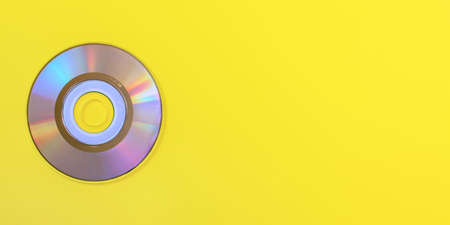 Top down view, small CD shiny / rainbow side, on yellow board, space for text on right side.
