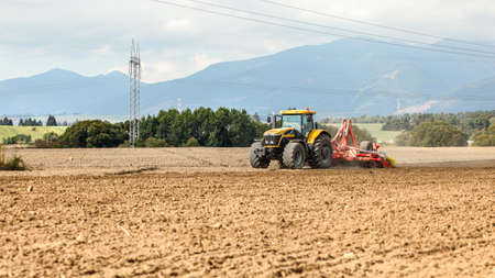 Yellow tractor pulls red sowing trailed over dry field, small trees and mountains in background. 版權商用圖片