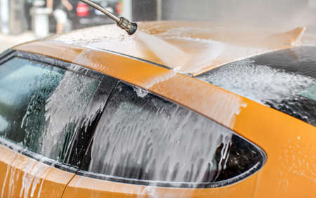 Yellow car washed in self serve carwash, water jet spray cleaning up the shampoo and foam from the roof and windows. 版權商用圖片