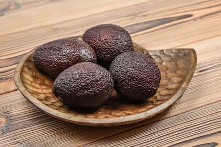 Four ripe brown avocados on wooden carved bowl.
