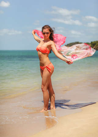 Young woman wearing bikini standing on wet sand at the beach, holding scarf waving in wind. Clear sea and sky background