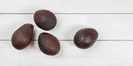 Top down view, four ripe brown avocados on white boards desk. 版權商用圖片